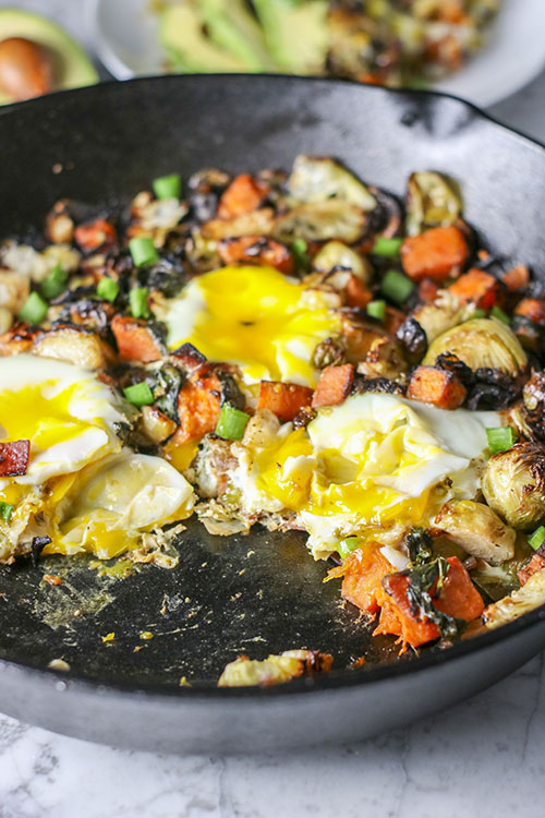 You will LOVE everything about this Healthy One Skillet Breakfast Hash - Tender sweet potatoes, nutrient-rich spinach, and roasted brussel sprouts, sprinkled with flavorful Canadian bacon, and topped with deliciously runny, baked eggs. Add sliced avocado and diced green onions for the perfect final touch! | NOMaste Kitchen