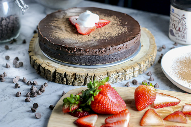 This flourless chocolate cake is the definition of decadence. Dense chocolate cake, drenched in sweet chocolate ganache. Like fudge - but better, because its cake.Amazing with milk, ice cream, strawberries, and/or whipped cream... you cannot go wrong with this incredible dessert | NOMaste Kitchen