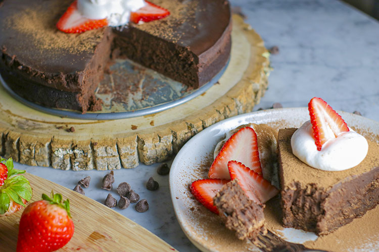 This flourless chocolate cake is the definition of decadence. Dense chocolate cake, drenched in sweet chocolate ganache. Like fudge - but better, because its cake. Amazing with milk, ice cream, strawberries, and/or whipped cream... you cannot go wrong with this incredible dessert | NOMaste Kitchen