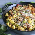 This One Skillet Chicken Sausage and White Bean Gnocchi is just as amazing as it sounds! Flavorful chicken sausage is sauteed with onion and garlic, then roasted with tomatoes, oregano, paprika, and my favorite - brussel sprouts! Baked with mozzarella & parmesan to complete this amazing one skillet meal. | NOMaste Kitchen