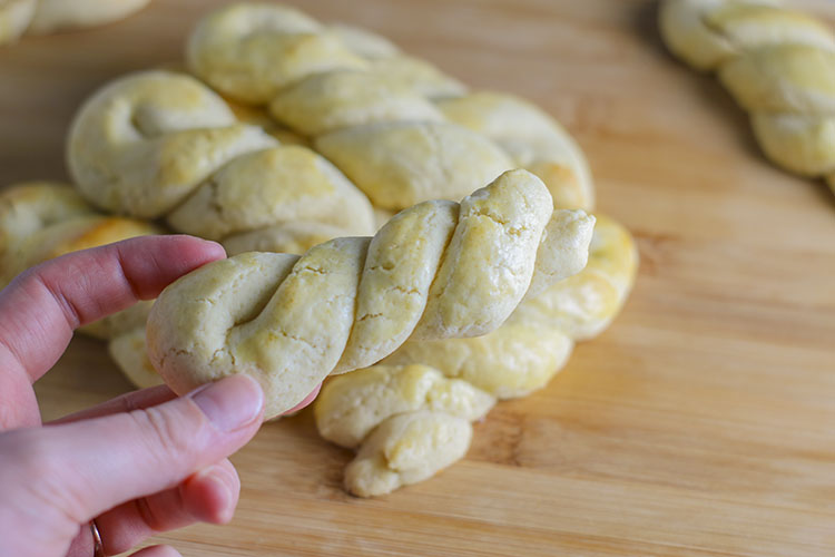 Sweet, dense, braided Greek butter cookies, perfect with a cup of coffee or tea! These melt-in-your-mouth sweet vanilla almond morsels are incredibly easy to make and even more delicious to eat! One Koulourakia will just not be enough! | NOMaste Kitchen