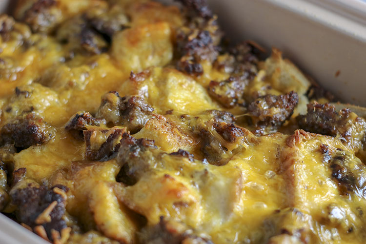 This Sausage, Egg, and Cheese Breakfast Casserole is a special occasion / treat yourself kind of breakfast casserole recipe! Easy to make - easier to eat! Soft white bread soaked overnight in rich egg, then sprinkled with salty, crumbled sausage and LOADS of cheddar cheese. Baked to perfection | NOMaste Kitchen