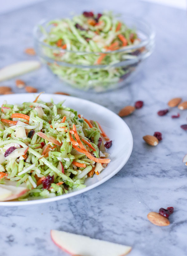 Crisp, light and refreshing - this Cranberry, Apple, and Almond Broccoli Slaw is the perfect side for a BBQ, picnic, or weeknight meal. Fresh, juicy apples, sweet, bright cranberries, and crunchy almonds fill this salad with flavor and incredible texture. Tart red wine vinegar is balanced by a sweet touch of honey | NOMaste Kitchen