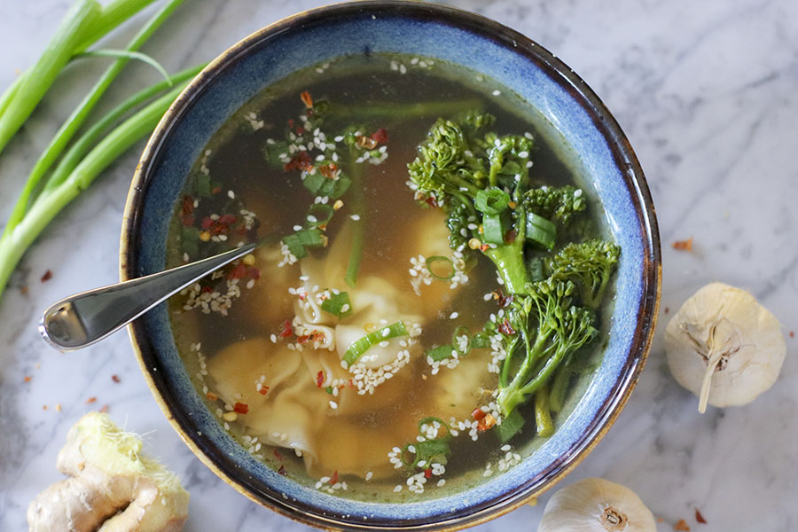 This EASY Wonton Soup is warm and light, yet richly satisfying. Flavorful garlic and ginger balanced by salty soy sauce and a touch of sesame oil - each wonton is like a little pocket of joy in your mouth. This is the perfect soup to warm you up on a cold day in winter, or spring! | NOMaste Kitchen