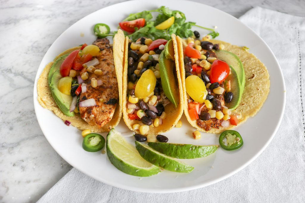 These Easy Fish Tacos are PERFECT for summer! Bright and bold, with just a touch of heat - Top with black bean and corn salad, avocado, and more! | NOMaste Kitchen