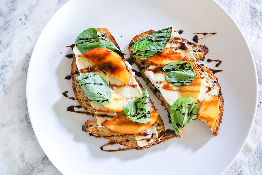 Camembert and Peach Toast with Balsamic Glaze - Creamy camembert cheese, juicy peach, and fresh basil make for a wonderful summer toast - top with an easy balsamic glaze and you've found perfection | NOMaste Kitchen