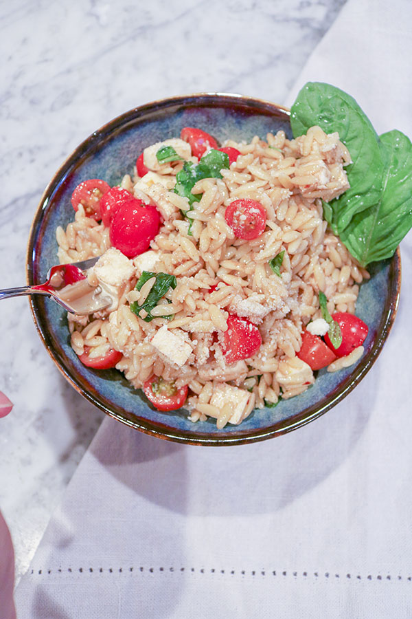This Caprese Pasta Salad is easy and perfect - Al dente orzo, creamy mozzarella, juicy tomatoes, and fresh basil all tossed with a light vinaigrette. | NOMaste Kitchen