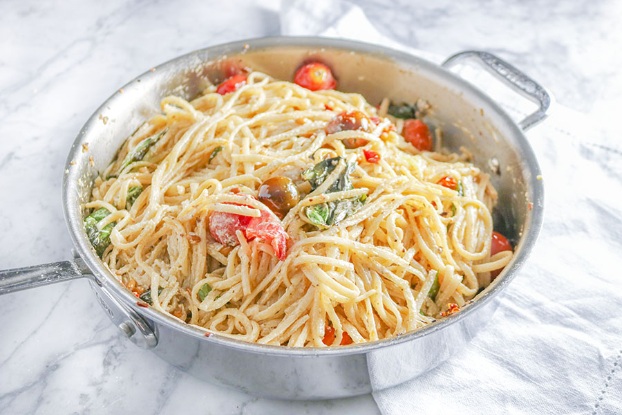 This Tomato Basil and Goats Cheese Pasta is perfection! Tossed with sauteed pine nuts, roasted tomatoes and fresh basil. Creamy, light, and delicious! | NOMaste Kitchen