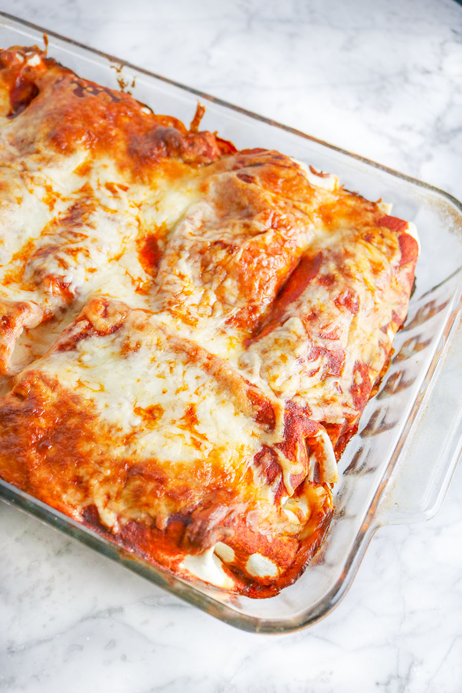 Loaded with beans and chicken, these cheesy, saucy Chicken Enchiladas are an easy and perfect weeknight meal that the whole family will enjoy! | NOMaste Kitchen