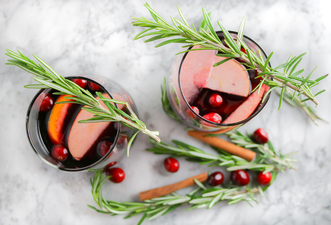 Fresh, festive, and delicious - this Christmas Sangria is the perfect addition to your holiday tradition! Cinnamon, cranberries, rosemary... | NOMaste Kitchen