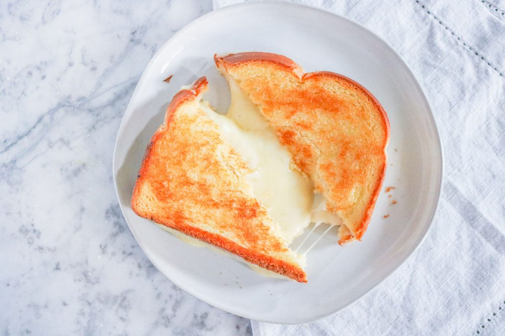 The ultimate buttery, cheesy, delicious sandwich that kids (and adults) will love. This Grilled Cheese is the definition of perfection. | NOMaste Kitchen