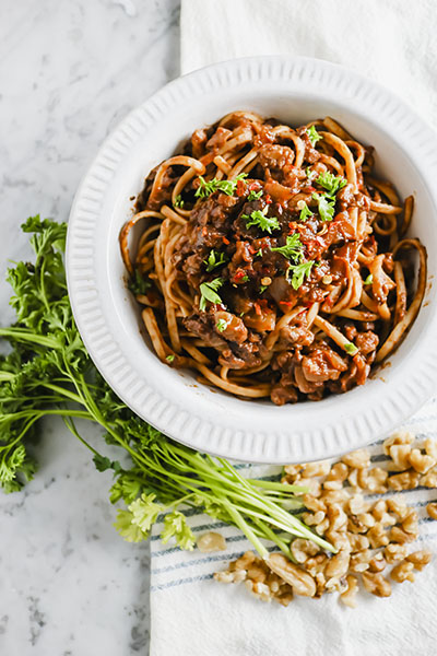 Meat equals hearty, but hearty does not have to equal meat! This delicious Mushroom & Walnut Vegan Bolognese proves just that! Enjoy over any type of pasta! | NOMaste Kitchen