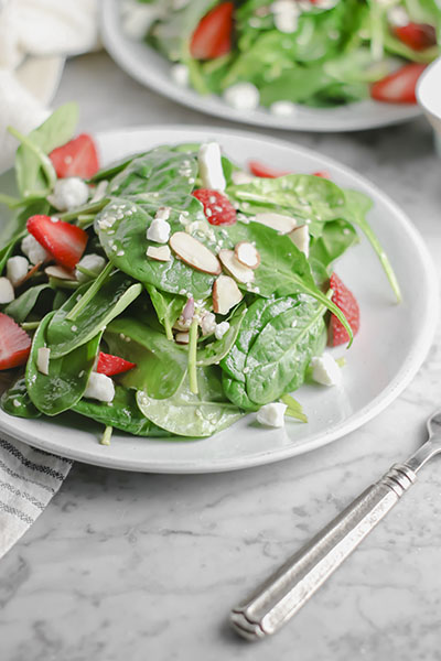Fresh spinach, juicy strawberries, creamy goats' cheese, crunchy almonds - This Strawberry Almond Goat Cheese Salad is MADE by its toasted sesame DRESSING! | NOMaste Kitchen
