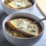 This Easy French Onion Soup is incredible! Rich, flavorful beef broth, loaded with onions and seasoned to perfection with sherry and thyme. Topped with baked bread and delicious ooey gooey Swiss cheese. The perfect bowl of satisfying deliciousness to warm you up on a cold day!